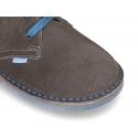 Zapatito tipo blucher con lengüeta, cordones y suela combinado en piel serraje.