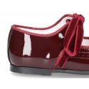 Classic patente leather little mary janes angel style with velvet shoelaces.