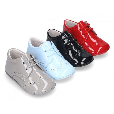 Laces up style shoes for babies in patent leather.