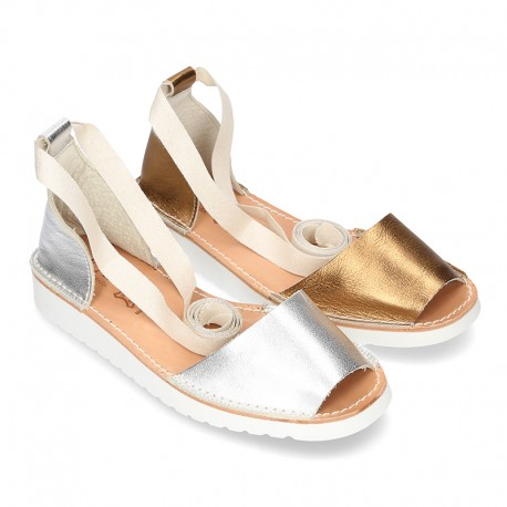 New halter Menorquina sandals in metal leather with crossed ribbons.