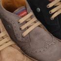 Bota tipo zapatilla con picados y cordones en piel serraje.