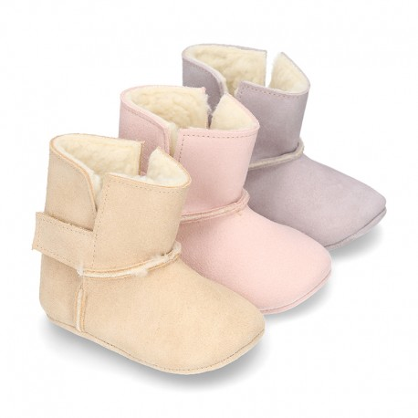 Liittle lined baby bootie with hook and loop strap closure in suede leather.