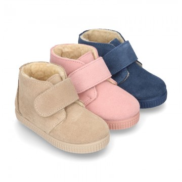 New suede leather little bootie sneaker style with fake hair lining and velcro strap.