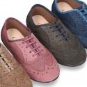 Zapato clásico tipo Blucher con lazos y picados en piel serraje.