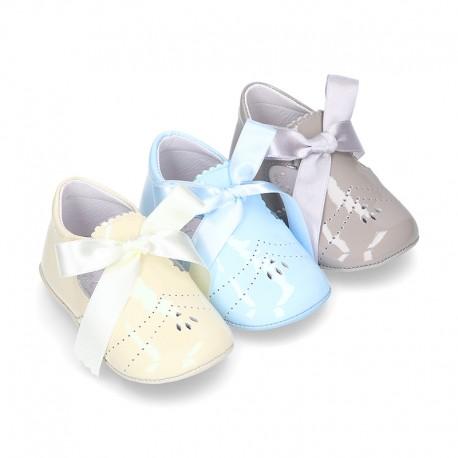 Angelito para bebés con lengüeta y lazo en piel charol.