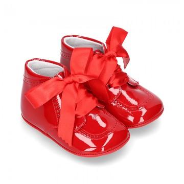 Botita bebé con picados y lazos en charol rojo.