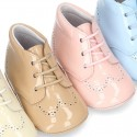 Little ankle boots for babies with shoelaces closure in patent leather.