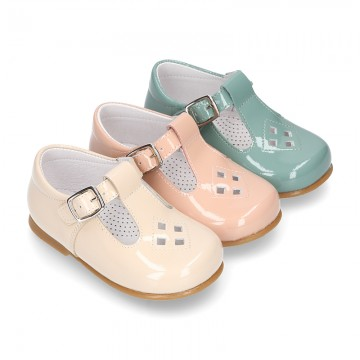 Little T-Strap shoes with perforated design in patent leather in pastel colors.