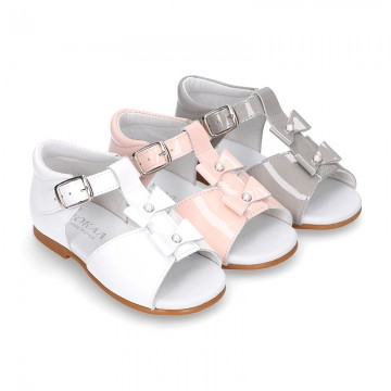Patent leather Little T-Strap Sandal shoes with buckle fastening and with bows and pearls design.