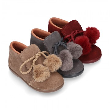 Booties with shoelaces closure with POMPONS in suede leather for kids.