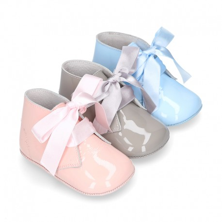 Patent leather little bootie for babies with silk ties closure design.