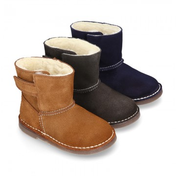Suede leather Boots with velcro strap closure and fake hair lining.
