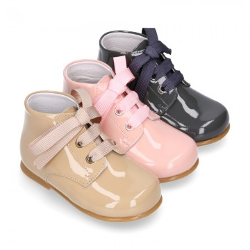 Classic pastel color patent leather ankle boots to dress with ties closure for first steps.