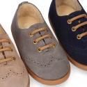 Zapato tipo Blucher niño con cordones y picados en piel serraje.