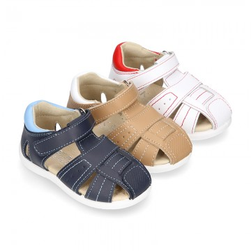 Washable leather kids sandal shoes with crossed straps and hook and loop strap closure.