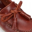 Moccasin shoes with bows and tassels in leather color for toddler boys.