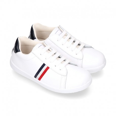 Washable leather OKAA kids School tennis shoes with laces and flag design.