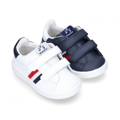 Washable leather tennis shoes laceless and with flag design.